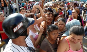 People queue to buy toilet paper and nappies outside a pharmacy in Caracas.