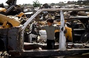 Khan Yunis, Gaza Strip: A Palestinian boy plays in an abandoned vehicle