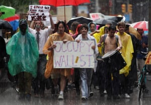 Occupy Wall Street demonstrators march in the rain through the streets of the financial district of New York on 29 September 2011.