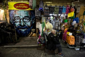 A shop owner sits next to his stall which has been decorated with a portrait of Steven Spielberg