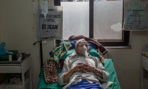 A man affected by lung cancer lays on his bed inside one of the rooms at the Bhaktapur Cancer Hospital in Bhaktapur, Nepal.