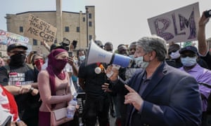 Kenosha Mayor John Antaramian, tries to speak to protesters using a megaphone on Monday afternoon
