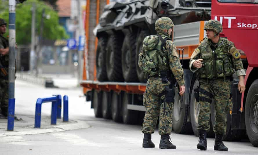 Police officers stand next to a lorry loaded with a damaged armoured personnel carrier in the northern Macedonian town of Kumanovo.