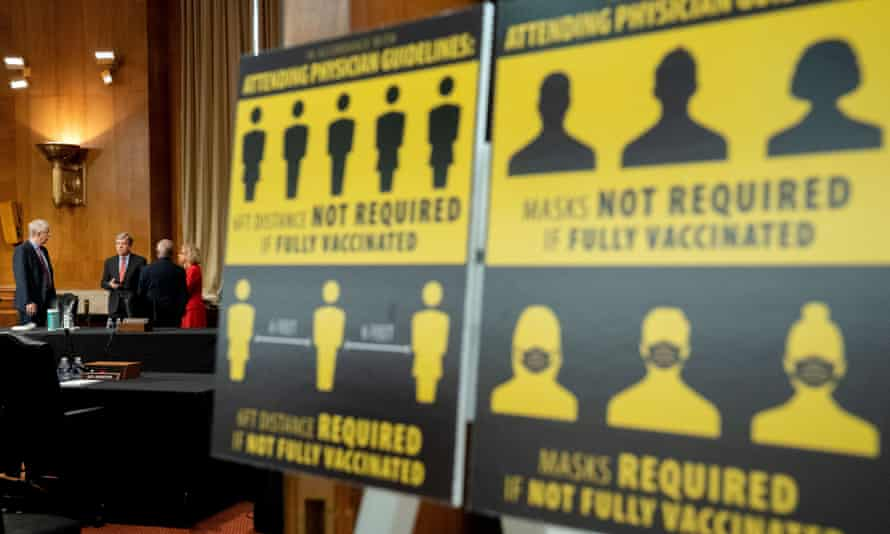 Francis Collins, at far left, waits for a May congressional hearing next to signs requiring masks if not vaccinated against Covid-19.