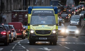 An ambulance driving along a busy street