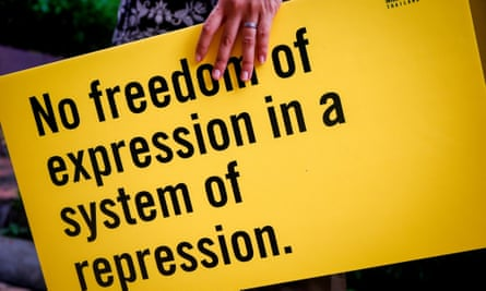 A woman holds an Amnesty placard saying 'No freedom of expression in a system of repression'