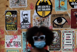 A demonstrator walks past a mural for George Floyd during a protest near the White House
