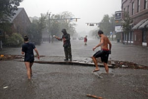 People survey the damage caused by Hurricane Florence on Front Street in downtown New Bern, North Carolina.
