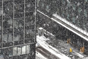 A worker cleans the snow from the sidewalk in Midtown Manhattan as snow falls again in the city