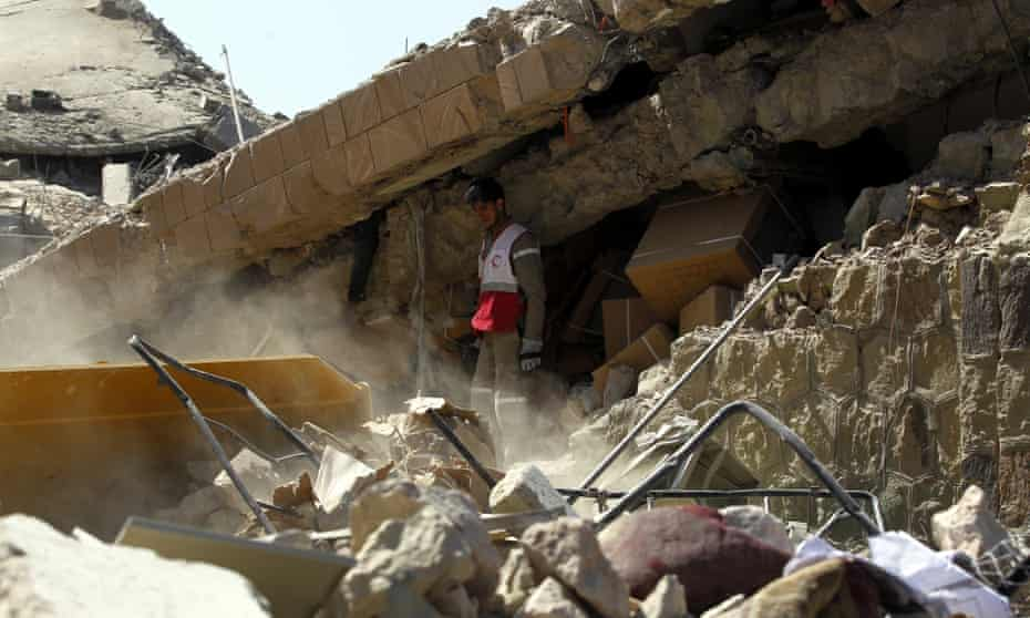 A medic searches for victims under the rubble left by a Saudi-led airstrike on the Yemeni capital, Sana'a.