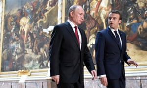 Emmanuel Macron (R) and Vladimir Putin (L) arrive for a joint news conference after a working meeting at the Versailles Palace, near Paris