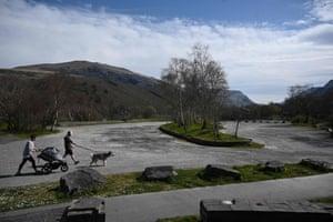 A couple walk through the empty car park near Llyn Padarn, a lake in Snowdonia