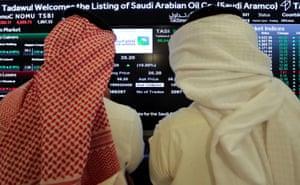 Investors monitoring a screen displaying stock information at the Saudi Stock Exchange (Tadawul), in Riyadh.