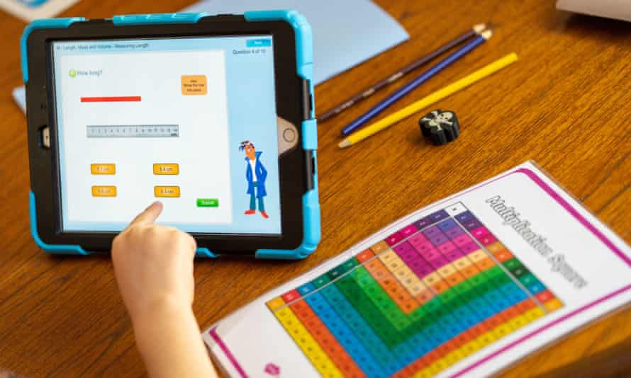 A child (out of shot) looking at a tablet computer and charts on a table