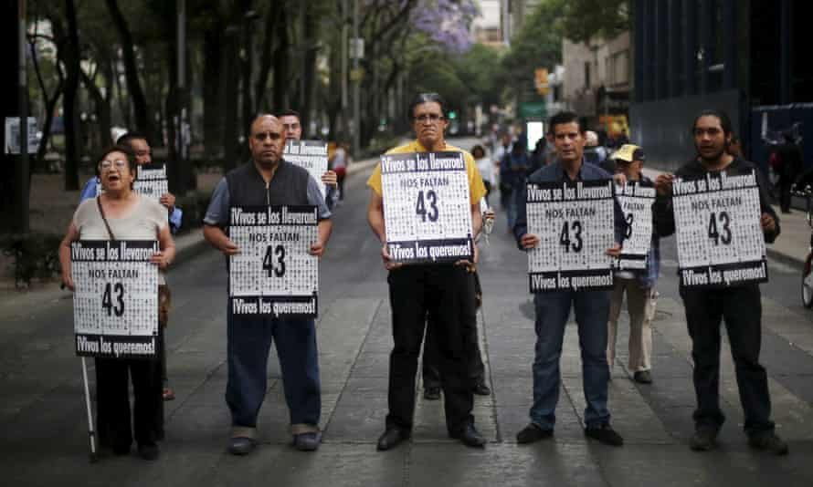 Activists in Mexico City hold signs to demand justice for the 43 missing students.