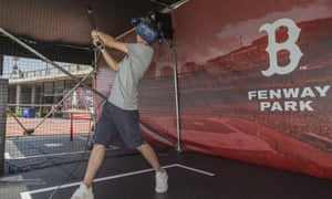 A Boston Red Sox fan practises his batting swing virtually against a photographic background of Fenway Park.