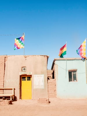 """Small, basic houses fly multi-coloured flags for independence day in Bolivia.  """"On a road trip to the Eduardo Abaroa Andean Fauna national reserve and the Salar de Uyuni, we stopped in this tiny village. The Bolivia and Quechua flags were out for independence day."""""""