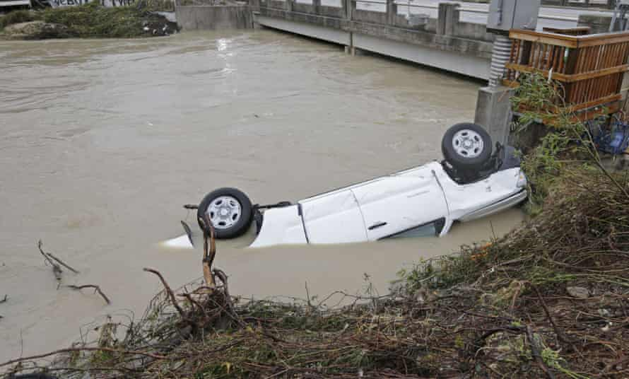 A pickup truck rests against the side of Gills Creek near a bridge in Columbia, South Carolina, on Monday.