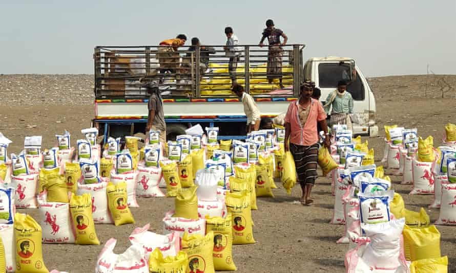Displaced Yemenis receive food aid donated by a British organisation in Yemen's western province of Hodeida.