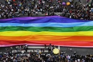 Participants extend a huge rainbow flag