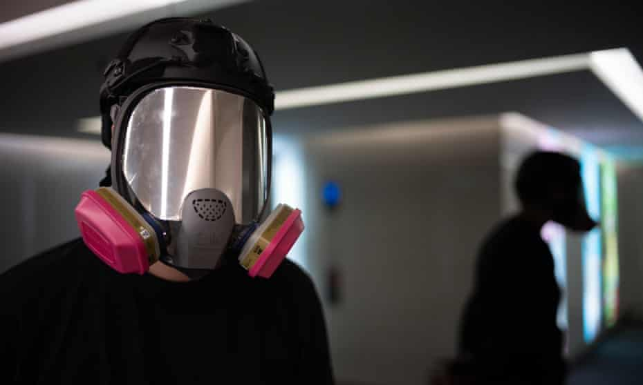 Ryan Lee in a full-face gas mask and black clothing