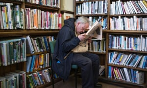 A short sighted man reading a newspaper in the old Aberystwyth Carnegie funded public lending library, Wales UK