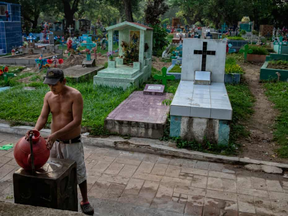 Victor fills up the a large pitcher with potable water at a cemetery tap.