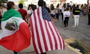 People with the Mexican flag and the US flag take part in a rally against hate one day after a mass shooting at a Walmart store in El Paso, Texas.