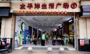 Staff members sit at the entrance of a mall to check for Covid-19 vaccination credentials in the Yangpu District of Shanghai, China, 7 June.