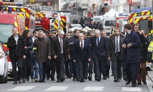French interior minister Bernard Cazeneuve (centre), Paris prosecutor Francois Molins (third left) and prefect of police Michel Cadot (third right) arrive in a security perimeter in St-Denis