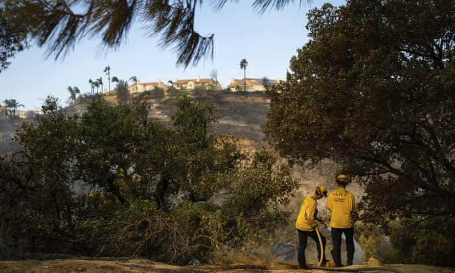 Los Angeles county firefighters work hot spots in the Porter Ranch area of Los Angeles, on Friday after the Saddleridge fire burned through thousands of acres.