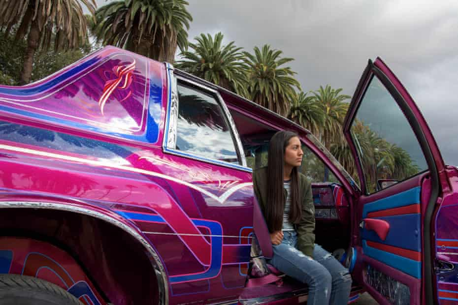 woman sits on passenger side of brightly colored pink lowrider