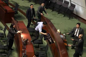 Security officers pursue pro-democracy lawmaker Au Nok-hin as he leaps across desks to chase Hong Kong chief executive Carrie Lam during a question and answer session at the legislative council.