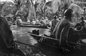Caught in a sudden monsoon rain, part of a company of about 130 South Vietnamese soldiers moves downriver in sampans during a dawn attack on a Viet Cong camp, January 10, 1966