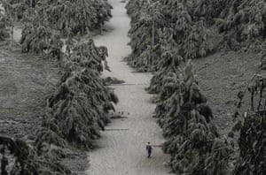 Tagaytay, Philippines: a man walks on a road covered with volcanic ash from the erupting Taal volcano