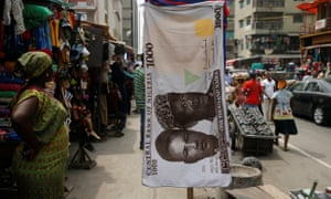 A towel with a print of the Nigerian naira is displayed at a street market in the central business district of Lagos, Nigeria's commercial capital