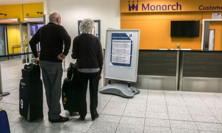 Monarch passengers read message board in airport