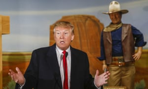 Donald Trump speaks in front of a statue of actor John Wayne after receiving the endorsement of Wayne's daughter Aissa Wayne during a campaign appearance at the John Wayne Museum in Winterset, Iowa, on 19 January 2016.