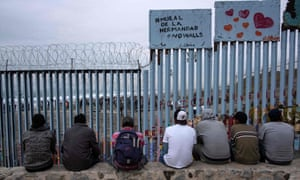 Men sit next to a sign reading 'mural of brotherhoood' look at the US-Mexico border fence from Playas de Tijuana in Baja California.