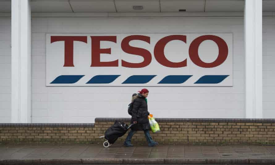 Tesco exterior with female shopper walking past logo