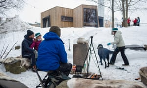 The Tangeraas family sit around the fire in the grounds of Oslo University hospital.