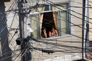 As mulheres observam um protesto contra a violência entre policiais e gangues que colocaram os residentes no fogo cruzado na favela do Complexo da Mare do Rio de Janeiro.