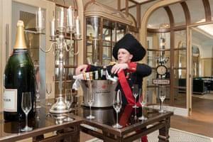 A champagne waiter welcomes the guests for the weekly Versailles Decadence Brunch at the luxury St Regis Hotel.