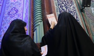 Two women cast their votes in Iran's parliamentary elections on Friday.