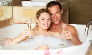 couple relaxing in bath drinking champagne