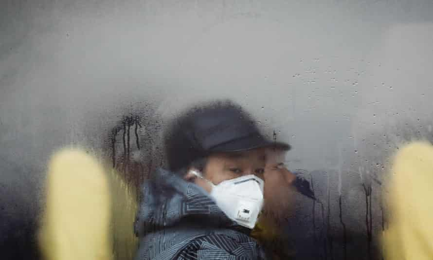 A man wearing a mask looks out from a bus in Beijing as the city is blanketed by smog, Dec 2016