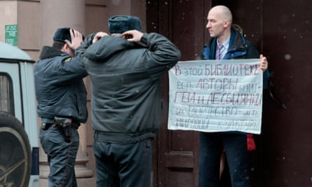 "Policemen approach to check a passport of a gay rights activist standing in individual picket in St.Petersburg, Russia, Wednesday, April 4, 2012. His poster reads: ""In this library there are also books by gay and lesbian writers. Their works are a part of the world culture""."