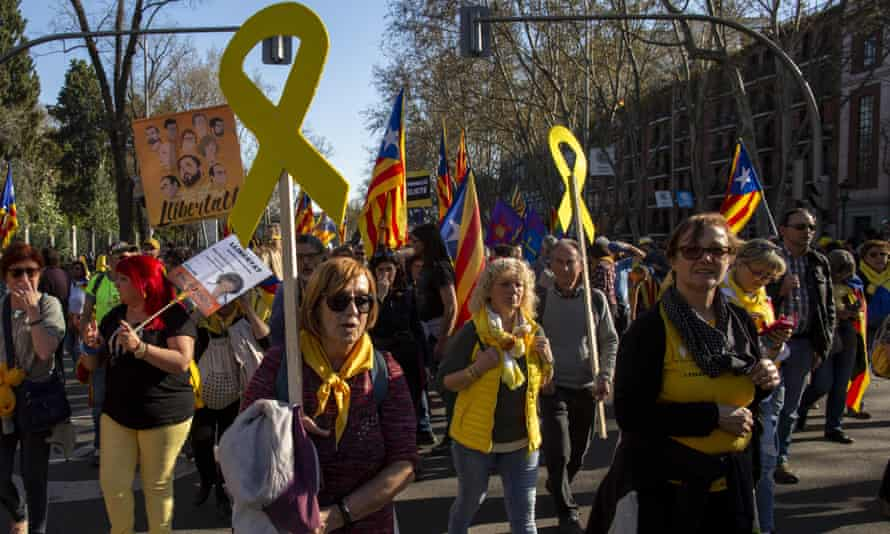 Protesters carry Catalan Independence flags and yellow ribbons.