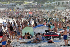 Beachgoers are seen at Bondi beach in defiance of social distancing rules banning gatherings of more than 500 people and mandating 1.5m between individuals in public areas.