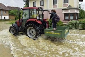 A woman is transported by tractor through a flooded street in Braunau am Inn, Austria